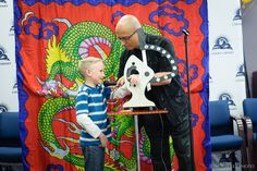 A magician entertains patrons at the Logan Library Centennial Carnival.