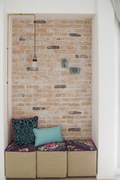פינת קריאה בתוך נישה.   הקיר יכול להיות מודגש בטפט או בצבע במקום בבריקים. שימי לב לגוף התאורה המעניין.