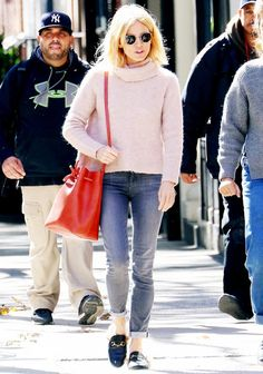 Sienna Miller pairs a Madewell turtleneck sweater with skinny jeans, loafers and a bucket bag.
