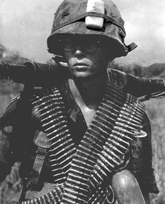A teenage U.S. soldier with an M60 and ammo belts on his shoulders - Vietnam War