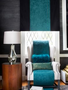 To accentuate the soaring height of the living room ceiling, the designers commissioned custom Roman shades featuring stripes made from teal Ultrasuede sewn directly down the centers. The stripe element carries downward from the Roman shade to the wingback chairs in the form of folded throw blankets made from the same Ultrasuede, which puddle onto the floor.