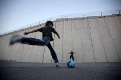 Niños palestinos juegan fútbol frente al muro de separación israelí en la villa de Abu Dis en Cisjordania, a las afueras de Jerusalén. (AFP/VANGUARDIA LIBERAL)