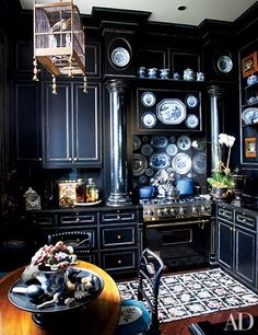 Friederike Kemp Biggs painted the kitchen cabinets in her New York penthouse with a rubbed finish of black over Chinese blue, limned in gold | archdigest.com