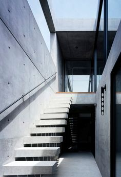 This house in Chiba, Japan, by Apollo Architects & Associates contains courtyards with elevated wooden walkways and glass walls behind its thick concrete exterior.  The building is set back from the frontal street where heavy vehicles pass by regularly. Parking space is secured for 3 cars. Reinforced concrete structure is chosen for its soundproofing ability. The opening is kept to a small horizontal ribbon window to block the noise & automobile emissions