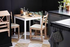 Una pequeña mesa de IKEA con dos sillas en un rincón de la cocina, preparada para desayunar.