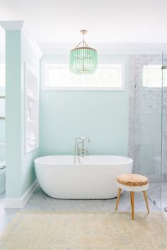 Bathroom with mint green walls, a mint chandelier, and a floating tub
