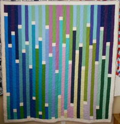 """48 solid strips with white in between. 69.5"""" x 64, 32 columns across.  Free pattern at http://www.e-quilterscorner.com/blog/2013/02/21/free-1600-jelly-roll-quilt-pattern/"""
