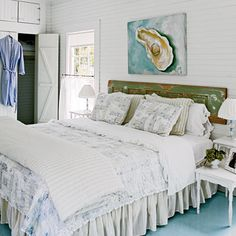 White beachy bedroom with wood white-washed closet doors and small side tables and chairs and headboard made out of door with chippy green paint