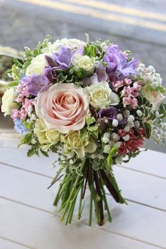 Soft pastel bridal bouquet featuring creams, pinks, purples, and blues. Designed by Stems, Innerleithen.