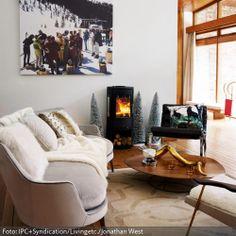 Das winterliche Wandbild, der Kamin, die Deko-Tannen und das Schaffell vermitteln Winter-Feeling pur. Die weichen Textilien sorgen in Kombination mit den gedeckten Farben und dem prasselnden Feuer für eine wohlige Wohnatmosphäre.