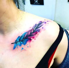 A colorful tattoo of a feather, inked on the collar bone. Style: Watercolor. Color: Colorful. Tags: Elegant