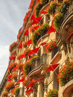 Flowers in Hanging Baskets...on Balconies...ona Beautiful & Artistic Buliding...with RED Awnings! Gorgeous!