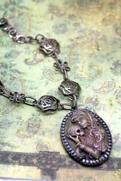 This memorizing necklace was created with handprinted cameo, in a lush bronze patina to show off all the very fine details from the stitch marks to the locks of hair! She has been sealed for long last