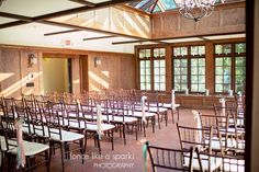A wedding ceremony in the conservatory at Willowdale Estate.  The simple ribbon isle decor looks great with our ballroom chairs!  Candles line the windows, and benches.    photo: http://www.oncelikeaspark.com/ venue: http://willowdaleestate.com