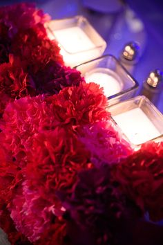 Indian wedding centerpiece with candles and pink and red flowers via IndianWeddingSite.com