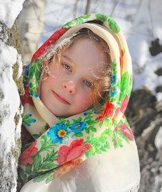 Kid in Russian clothes. This Russian girl in her traditional shawl looks like a real Snow Maiden.