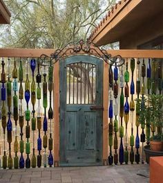 Beautiful wine bottle fence with restyled vintage door as a gate!!