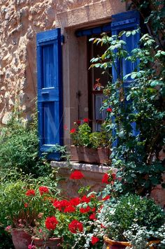 greek stone homes and flowers   ... shutters, flowers and vines growing on an old stone building. France