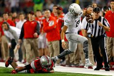 Quarterback Marcus Mariota #8 of the Oregon Ducks runs the ball ahead of cornerback Eli Apple #13 of the Ohio State Buckeyes during the College Football Playoff National Championship Game at AT&T Stadium on January 12, 2015 in Arlington, Texas. (Jan. 11, 2015 - Source: Tom Pennington/Getty Images North America)