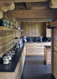 Chalet kitchen - Cuisine de chalet : Le plan de travail en marbre noir donne du relief à la pièce et fait ressortir la cuisine.