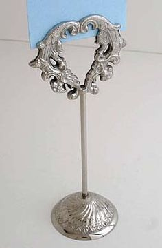 These heart-shaped nickel plated table number holders are so elegant. These table number holders are very heavy and in the victorian style. 8 inches tall. Sold as sets of 2 for as low as $26.95 in larger quantities. http://www.weddingaccents.com/accessories/Table-Number-Holders-p-3-c-296.htm