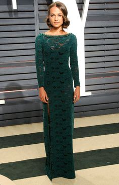 ALICIA VIKANDER swaps her frilly black Louis Vuitton for a streamlined forest green lace boatneck column and Bulgari jewels at the Vanity Fair afterparty.