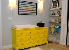 Love this yellow Dresser/change table.  The wall mounted abacus is cool and the Jonathan Adler Giraffe wall sconces.