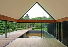 Glass walls slide back to open up this house extension to the surrounding English woodland