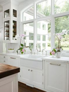 Stunning kitchen design with arched window, creamy white kitchen cabinets with marble countertops, wood panel dishwashers flanking farmhouse sink, marble slab backsplash, polished nickel Perrin & Rowe Bridge Faucet, orchids and white kitchen island with butcher block countertop..