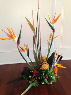 Flower school contemporary arrangement with birds of paradise, protea, spray roses, ti leaves, flax, snake grass