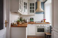 Hangulatos kis konyha, fehér bútor, fa munkapult, metro csempe hátfal és pasztellkék falak