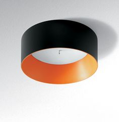 Artemide Tagora 570 ceiling-mounted luminaire for direct and diffused flourescent lighting. 57 cm. Aluminum in beige/white, grey/white, or black/orange. 	Design by S. & R. CORNELISSEN.