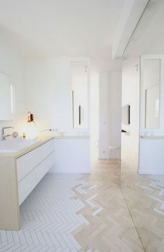 Bathroom in white and wood with a special herringbone floor made of wood and white tiles via The Style Files