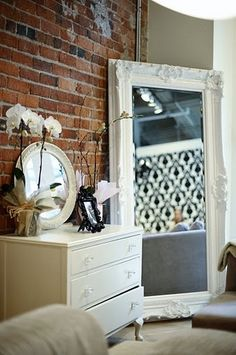 Our ornate Rococo mirror painted white and propped up against a brick wall