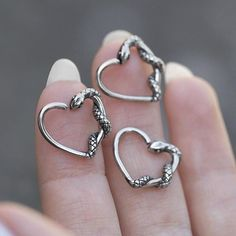 Continuous ring featuring a tiny Snake coiled around a heart. Ideal for daith piercings. #bodyjewellery www.regalrose.co.uk/products/slink-silver-snake-heart-daith-ring