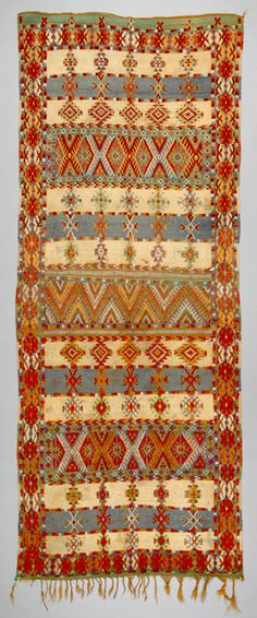 Africa | Floor rug ~ l'ahmal n'ibouli ~ from the Berber, Ait Ouaouzguite tribe living in the High Atlas Mountains of Morocco | ca. 1920 - 1940 | Wool; weft-faced, knotted pile | Traditionally, Ait Ouaouzguite Berber rugs were flat-woven in natural white and brown wool with twining applied in the horizontal bands. In this rug, borders and horizontal bands are woven in knotted-pile technique. This is a hybrid between the Ait Ouaouzguite flat-woven and knotted-pile carpets.