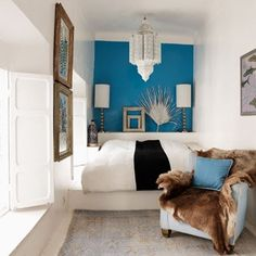 Electric blue feature wall in Moroccan-style small bedroom with white chandelier and raised platform bed