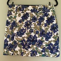 Brooks Brothers skirt in pretty floral  Brooks Brothers floral skirt in size 6. Heavier  weight fabric keeps skirt laying nicely. Fully lined. Classic tailoring.  Buttons in front are decorative. Pretty floral pattern on white. Floral in olive, blue, green, Black and Tan. Size 6. Excellent condition. Brooks Brothers Skirts A-Line or Full