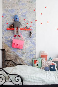 A creative way you mix Wallstickers with art, cushions and colors.  ferm LIVING Cushions - http://www.fermliving.com/webshop/shop/kids-room/kids-cushions.aspx  ferm LIVING Dots Wallstickers -http://www.fermliving.com/webshop/shop/mini-dots-wallsticker-1.aspx   ferm LIVING Harlequin Wallpaper Mint - http://www.fermliving.com/webshop/shop/kids-room/kids-wallpaper/harlequin-wallpaper-mint.aspx
