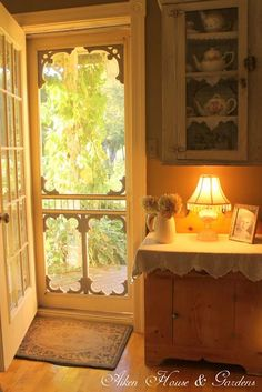I love everything about this small scene: Lovely screen door - I want my screen doors that decorative! Warm colors, love the cloth laying on the cabinet top, everything.