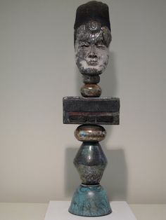 This work , a totemic piece is created in a primitive style and is fired in the Raku technique, producing a rich complex patterning of cracled glazes and metallic elements. (The second photo is a close-up of only the top section-It stands 30 high and is 10 at its widest area. It is comprised of separate sections that fit together , with each piece having its own character and relating to the whole.