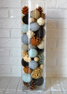 Glass cylinder filled with painted styrofoam balls (from Michaels) and mixed with pack of decorative balls and pine cones from Home Goods.