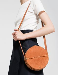 """From Rachel Comey, a modern crossbody bag in Melon. Features round design, suede construction, magnetic closure, gold-tone hardware, adjustable strap and exterior gold tone metal """"RC"""" logo. Unlined.  •Crossbody bag in Melon •Round design •Suede con"""