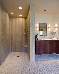 This bathroom's walk-in shower looks organic and brings nature in. Photo by Kaufman Homes, Inc.