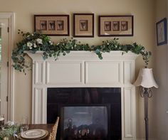 Simple greenery with emphasis on left with white flower accents on mantel.