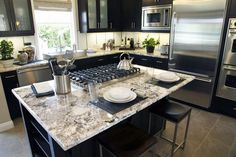 Custom kitchen island with a stovetop and granite breakfast bar (love the colors & ADORE the countertops!)