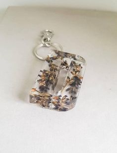 This initial keyring is made using layers of resin and real Lavender flowers. This Lavender keyring measures 5 cm long approximately 3 cm wide (slight variance for some letters) and approximately 1 cm thick. This large letter keyring would be a great gift for that special someone