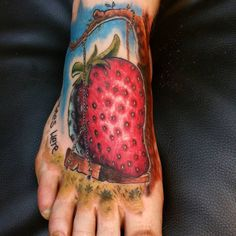Tattoo on the foot of the girl - strawberries