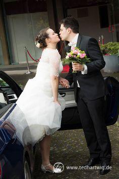 Die Braut steigt aus dem Brautauto, der Bräutigam empfängt sie überglicklich.