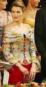 Vestido de Lorenzo Caprile de falda sirena de raso en color guinda y un corpiño con flores brocadas en hilo de oro de escote barco.